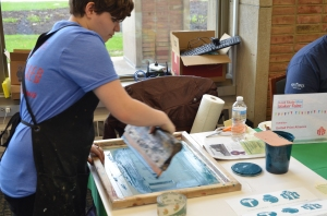 Stephanie Mote, Kent State student and member of the campus organization, United Print Alliance, offers a screen printing demonstration